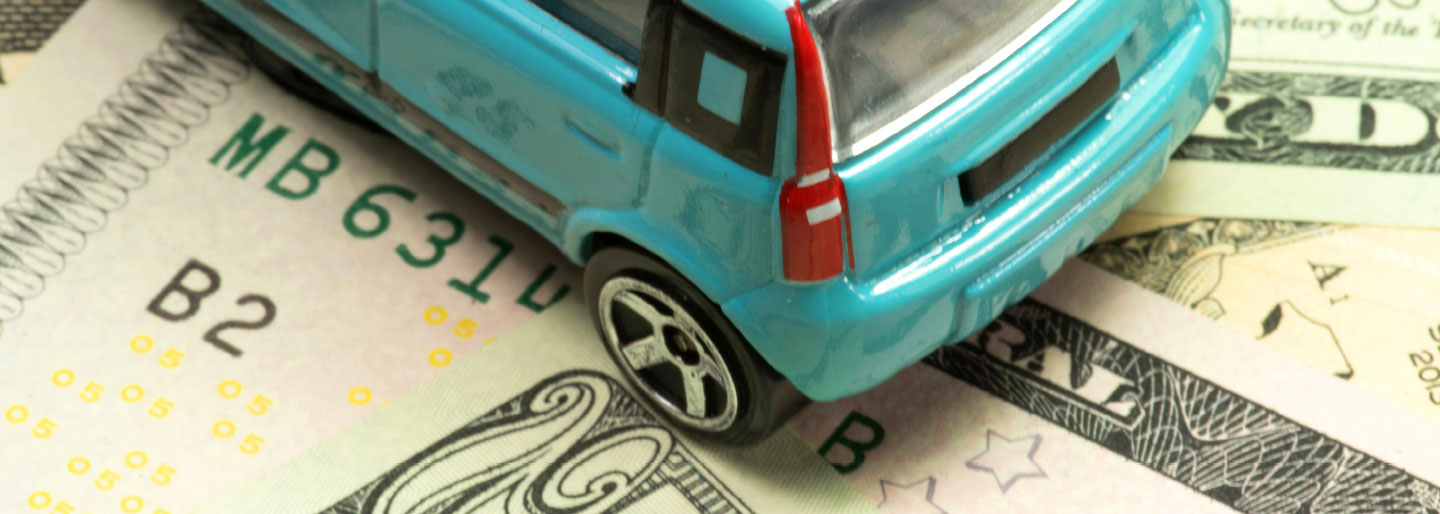 A toy car on a stack of bills.